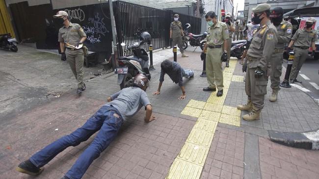 Petugas gabungan memberikan hukuman push up kepada warga yang tidak memakai masker saat razia Pembatasan Sosial Berskala Besar di Jakarta, Selasa (28/4). (ANTARA FOTO/Reno Esnir)