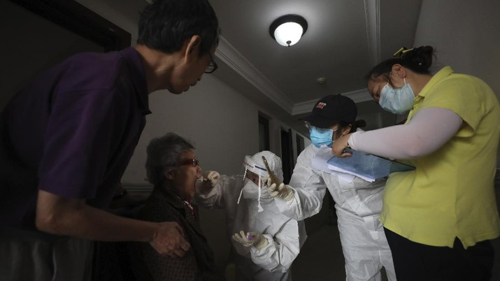 A medical worker takes a swab from a resident for the coronavirus test during home visits in Wuhan the epicenter of China's coronavirus outbreak in central China's Hubei province, Thursday, May 14, 2020. Some residential compounds in Wuhan have begun testing inhabitants for the coronavirus as a program to test everyone in the Chinese city of 11 million people in 10 days got underway. (Chinatopix via AP)