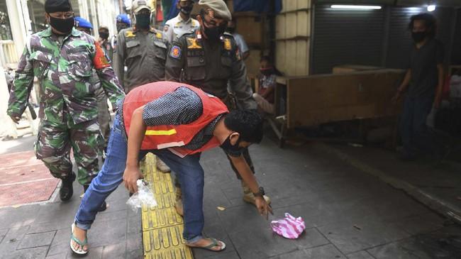 Pelanggar juga akan dikenakan rompi bertuliskan 'pelanggar PSBB' saat membersihkan fasilitas umum. (ANTARA FOTO/Akbar Nugroho Gumay)