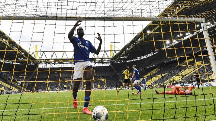 Schalke's Salif Sane reacts in the goal after Dortmund's Raphael Guerreiro scored his side's second goal against Schalke's goalkeeper Markus Schubert, right, during the German Bundesliga soccer match between Borussia Dortmund and Schalke 04 in Dortmund, Germany, Saturday, May 16, 2020. The German Bundesliga becomes the world's first major soccer league to resume after a two-month suspension because of the coronavirus pandemic. (AP Photo/Martin Meissner, Pool)