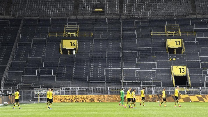 Dortmund players enter the pitch for the German Bundesliga soccer match between Borussia Dortmund and Schalke 04 in Dortmund, Germany, Saturday, May 16, 2020. The German Bundesliga becomes the world's first major soccer league to resume after a two-month suspension because of the coronavirus pandemic. (AP Photo/Martin Meissner, Pool)