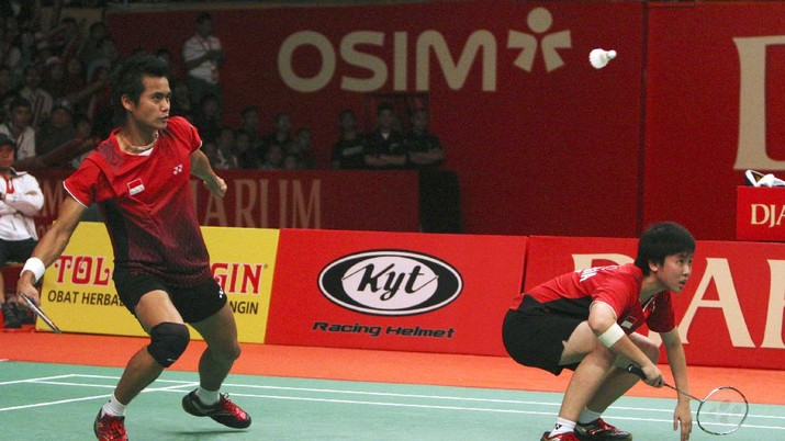 Indonesia's Ahmad Tantowi, left, returns a shot as teammate Lilyana Natir looks on in their mixed doubles final match against China's Zhao Yunlei and Zhang Nan at Djarum Indonesia Open badminton championship at Istora stadium in Jakarta, Indonesia, Sunday, June 26, 2011. (AP Photo/Achmad Ibrahim)