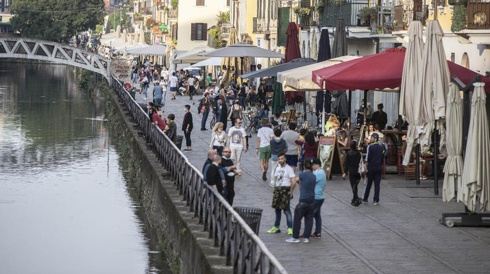 People walk at the Naviglio grande canal district in Milan, Italy, Monday, May 18, 2020. On Monday, Italians enjoyed a first day of regained freedoms, including being able to sit down at a cafe or restaurant, shop in all retail stores or attend church services such as Mass. (AP Photo/Luca Bruno)