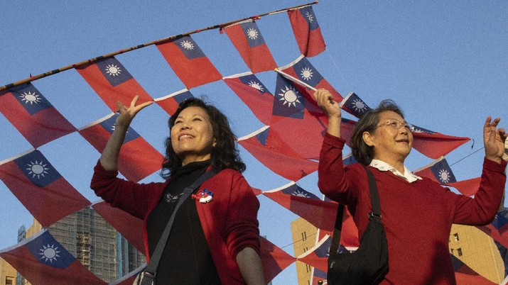 In this photo taken Thursday, Jan. 9, 2020, supporters of the Nationalist or KMT party pose with the Taiwanese flag during a rally for the presidential election in Taipei, Taiwan. About two-thirds of Taiwanese don't identify as Chinese, according to a survey released Tuesday, highlighting the challenge China faces to bringing the self-governing island under its control. The U.S.-based Pew Research Center found that 66 percent view themselves as Taiwanese, 28 percent as both Taiwanese and Chinese and 4 percent as just Chinese. (AP Photo/Ng Han Guan)