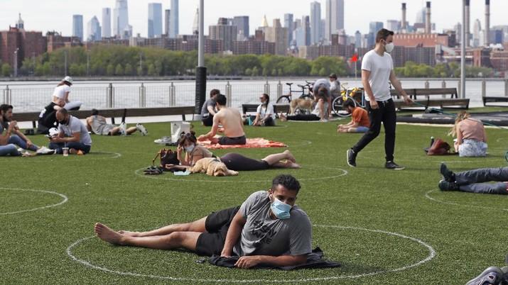Jaga jarak saat berjemur di taman New York. AP/Kathy Willens
