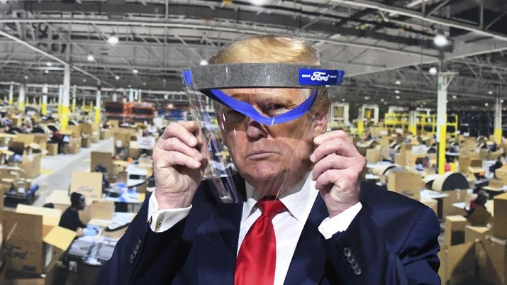 President Donald Trump looks through a face shield, in front of a poster of the manufacturing of the shields, while touring Ford Motor Co.'s Rawsonville Components Plant in Ypsilanti, Michigan on Thursday, May 21, 2020. (Daniel Mears/Detroit News via AP)
