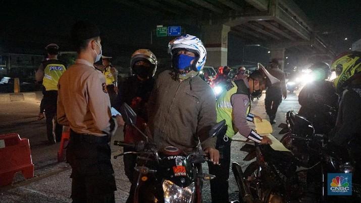 Petugas memeriksa kendaraan roda dua yang diduga untuk berpergian mudik di Jalan Raya Kalimalang, Jakarta Timur, Jumat (22/5). Dua hari jelang lebaran para pengendara motor masih ada yang nekat untuk pergi mudik. Petugas kepolisian dan Dishub memberhentikan motor yang memiliki muatan lebih. Pengendara motor diperiksa juga KTP asalnya. Jika ketahuan dari mereka mudik petugas menyuruh para pemudik motor untuk putar balik. Petugas kepolisian yang berjaga di check point jalan raya Kalimalang ini terus memantau, mengawasi dan melakukan pemeriksaan secara ketat agar pemudik yang berusaha keluar dari Jakarta bisa dihalau. Seperti diketahui Pengendara yang melintas masuk atau keluar ibu kota di 12 titik checkpoint, wajib menunjukkan SIKM. Ketentuan ini sesuai Peraturan Gubernur Nomor 47 Tahun 2020 tentang Pembatasan Berpergian Keluar Masuk DKI Jakarta. SIKM diperuntukan bagi warga yang karena tugas dan pekerjaannya harus melakukan perjalanan dinas keluar dan/atau masuk wilayah DKI Jakarta atau Jabodetabek selama masa pandemi.  (CNBC Indonesia/ Muhammad Sabki)
