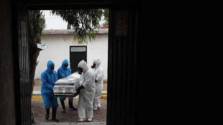Workers wearing protective gear carry the plastic-wrapped coffin of a person who died from COVID-19 into the crematorium at San Cristobal Mausoleums in Ecatepec, Mexico State, part of the Mexico City metropolitan area, Thursday, May 21, 2020. When handling cases of confirmed or suspected COVID-19, crematorium workers wear protective suits, full-face respirators, and gloves, and maintain strict disinfection protocols. (AP Photo/Rebecca Blackwell)