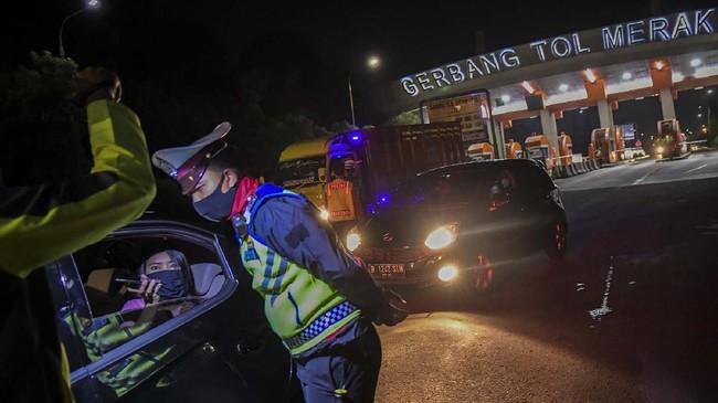 Petugas kepolisian memeriksa kendaraan di pintu Gerbang Tol Merak, Banten, Kamis (21/5/2020) malam, sebagai upaya penyekatan gelombang pemudik jelang Hari Raya Idul Fitri 1441 H. (ANTARA FOTO/Galih Pradipta)