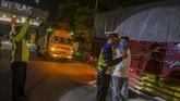 Petugas kepolisian memeriksa kendaraan yang melintas di pintu Gerbang Tol Merak, Banten, Kamis (21/5/2020) malam. (ANTARA FOTO/Galih Pradipta)