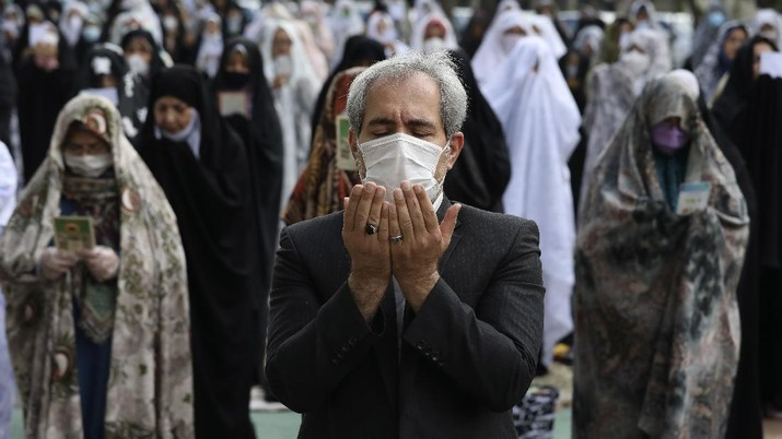 Worshippers wearing protective face masks offer Eid al-Fitr prayers outside a mosque to help prevent the spread of the coronavirus, in Tehran, Iran, Sunday, May 24, 2020. Muslims worldwide celebrate one of their biggest holidays under the long shadow of the coronavirus, with millions confined to their homes and others gripped by economic concerns during what is usually a festive time of shopping and celebration. In Iran, which has endured the deadliest outbreak in the Middle East, authorities have imposed few restrictions ahead of the holiday aside from cancelling mass prayers in Tehran traditionally led by Supreme Leader Ayatollah Ali Khamenei. (AP Photo/Vahid Salemi)