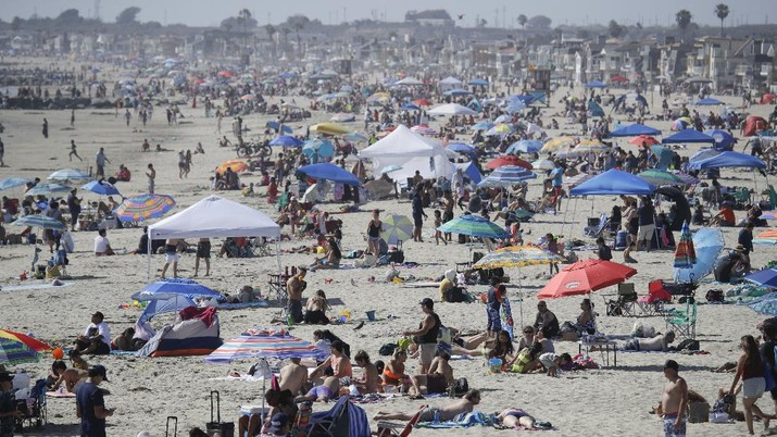 Visitors gather on the beach Sunday, May 24, 2020, in Newport Beach, Calif., during the coronavirus outbreak. (AP Photo/Marcio Jose Sanchez)