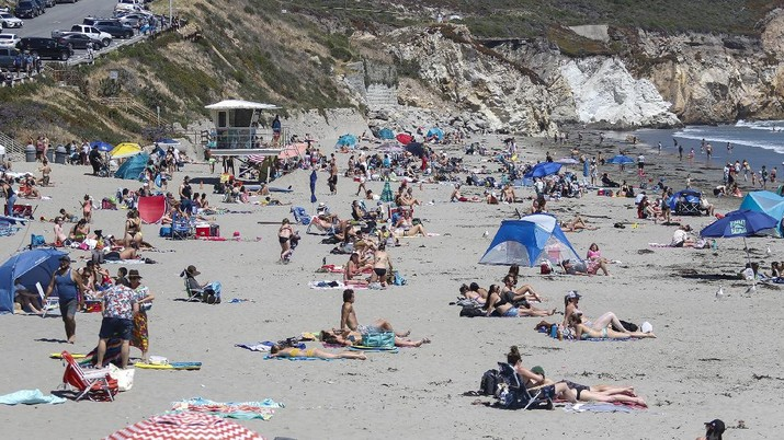 This Saturday, May 23, 2020, photo, shows a view of Avila Beach looking south from the Avila Beach Pier in Pismo Beach, Calif. The beaches in Pismo Beach and Avila Beach, California, were fairly packed with tourists during Memorial Day weekend with the coronavirus pandemic still ongoing. (Laura Dickinson/The Tribune (of San Luis Obispo) via AP)