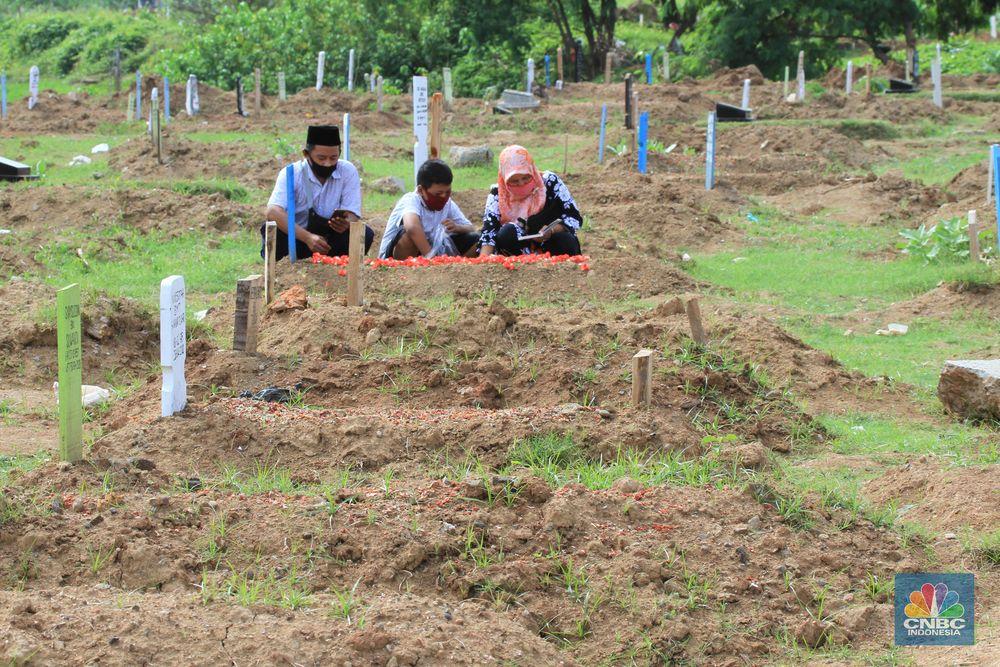 Taman Pemakaman Umum (TPU) Tegal Alur, Kalideres, Jakarta Barat, ramai oleh peziarah pada Hari Raya Idul Fitri 1441 Hijriyah, Ahad (26/5/20). Sejak pagi, keberadaan peziarah pada hari Lebaran ketiga tampak merata di blok pemakaman umum maupun blok makam khusus pasien Covid-19.      Terdapat pembatas garis polisi yang membedakan blok makam umum dan makam pasien Covid-19. TPU Tegal Alur diketahui merupakan salah satu makam yang khusus diperuntukkan jenazah pasien positif Covid-19.  Protokol kesehatan covid-19 diberlakukan secara ketat di kawasan TPU Tegal Alur. Peziarah wajib menggunakan masker dan mencuci tangan dengan sabun serta air mengalir. Selain itu, sebelum peziarah masuk dan keluar TPU Tegal Alur, terutama di blok makam pasien Covid-19, petugas melakukan disinfeksi kepada mereka.  Terik siang menyengat tak menghalangi niat peziarah berdoa di pusara keluarga yang telah wafat, seperti salah seorang pengunjung makam, Teguh (30). Bersama beberapa anggota keluarganya, Teguh berziarah ke makam ayahnya yang dimakamkan dengan protokol Covid-19 di TPU Tegal Alur.