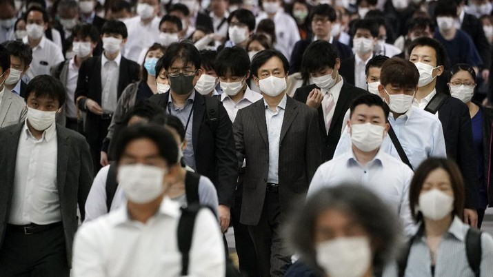 A station passageway is crowded with commuters wearing face mask during a rush hour Tuesday, May 26, 2020, in Tokyo.  Japanese Prime Minister Shinzo Abe lifted a coronavirus state of emergency in Tokyo and four other remaining prefectures on Monday, May 25, ending the declaration that began nearly eight weeks ago. (AP Photo/Eugene Hoshiko)
