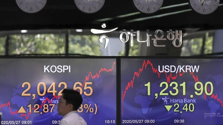 A currency trader talks near the screens showing the Korea Composite Stock Price Index (KOSPI), right, and the foreign exchange rates at the foreign exchange dealing room in Seoul, South Korea, Wednesday, May 27, 2020. Major Asian stock markets have declined as US-Chinese tension over Hong Kong competes with optimism about recovery from the coronavirus pandemic. (AP Photo/Lee Jin-man)