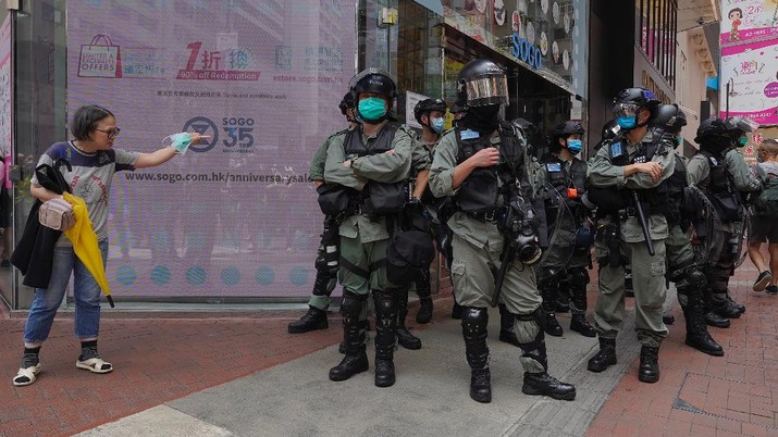 Riot police standing guard as a woman tries to cross the street in the Central district of Hong Kong, Wednesday, May 27, 2020. Hong Kong police massed outside the legislature complex Wednesday, ahead of debate on a bill that would criminalize abuse of the Chinese national anthem in the semi-autonomous city. (AP Photo/Vincent Yu)