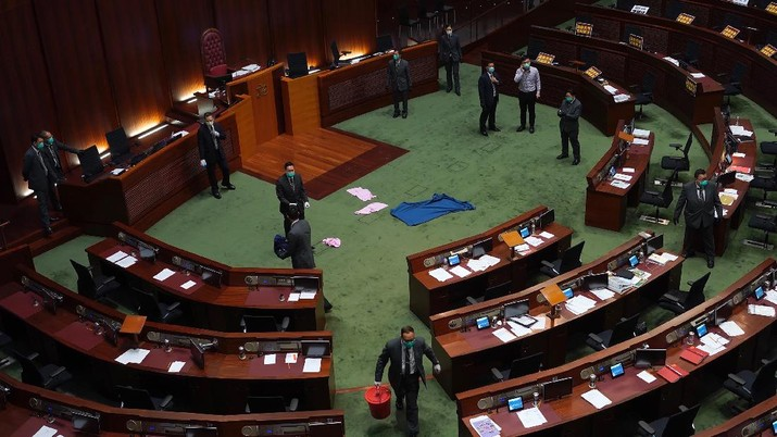 Staff from the Legislative Council cover the floor with towels after a pro-democracy lawmaker hurled an object during the second day of debate on a bill that would criminalize insulting or abusing the Chinese anthem in Hong Kong, Thursday, May 28, 2020. The lawmaker ejected later had spilled a substance on the floor that had to be cleaned up by firefighters wearing protective gear.(AP Photo/Vincent Yu)