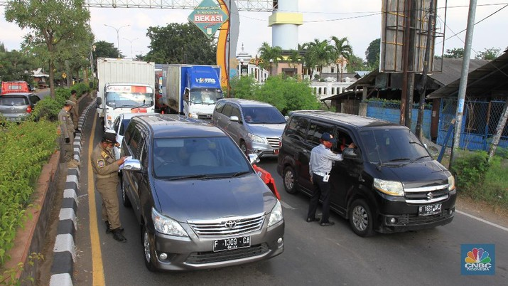 Petugas Dinas Perhubungan (Dishub) akan melakukan pemeriksaan terhadap pengguna kendaraan yang akan memasuki wilayah DKI Jakarta di wilayah perbatasan Bekasi-Karawang, Jawa Barat, Jumat (29/5/2020). Berdasarkan data Dishub Provinsi DKI Jakarta per Rabu (27/5) malam, sebanyak 6.364 kendaraan telah dikembalikan karena mencoba memasuki wilayah Jakarta tanpa memiliki Surat Izin Masuk-Masuk (SIKM) di masa arus balik Lebaran 2020. CNBC Indonesia/Tri Susilo   Tim Gugus Tugas Percepatan Penanganan Covid-19 Kabupaten Karawang, Jabar, menyatakan, terdapat delapan check point atau penyekatan kendaraan pemudik di wilayah Karawang.    Delapan titik check point itu di antaranya di Jembatan Tanjungpura, Jembatan Sian Djin Kupoh, Kobak Biru, Cibeet, Jembatan Rengasdengklok-Bekasi, Jembatan Batujaya-Bekasi, dan ada dua pos di Karawang Kota.    Pencegahan pergerakan pemudik itu berkaitan dengan upaya pemerintah yang melarang mudik pada Lebaran tahun ini sebagai bagian dari mencegah penyebaran virus corona.   Pantauan CNBC Indonesia dilapangan masih banyak pengendara yang masih melanggar peraturan yang sudah ditetapkan oleh pemerintah, contoh surat Surat Izin Keluar Masuk (SIKM).   Warga yang kedapatan tidak memiliki surat (SIKM) akan diputar balik.  Salah satu warga yang mudik dari Tegal, Jawa Tengah menggunakan sepeda motor diberhentikan oleh petugas pengaman perihal SIKM yang tidak ia miliki, tetapi dirinya mempunyai surat jalan untuk pulang ke Jakarta dari pihak kepolisian di Jawa Tengah.  (CNBC Indonesia/ Tri Susilo)