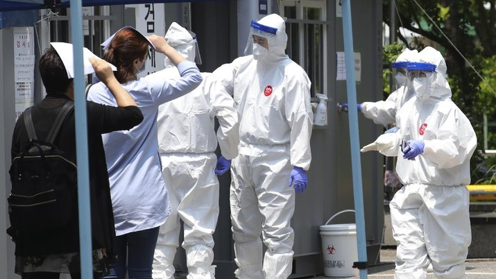 People suspected of being infected with the new coronavirus wait to receive tests at a coronavirus screening station in Bucheon, South Korea, Thursday, May 28, 2020. South Korea on Thursday reported its biggest jump in coronavirus cases in more than 50 days, a setback that could erase some of its hard-won gains. Health officials warned that the resurgence is getting harder to track and social distancing and other steps need to be taken. (Yun Hyun-tae/Yonhap via AP)