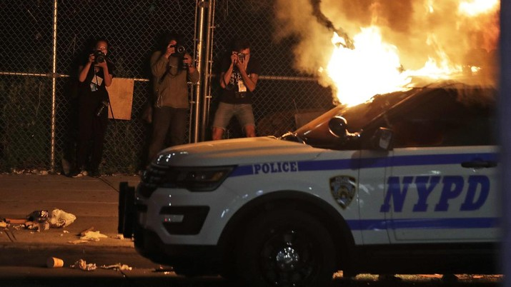Photographers take pictures of a burning police car in the Brooklyn borough of New York, Saturday, May 30, 2020. Demonstrators took to the streets of New York City to protest the death of George Floyd, a black man who was killed in police custody in Minneapolis on May 25. (AP Photo/Seth Wenig)