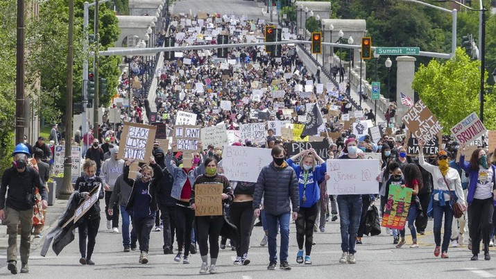 Crowds of protesters walk across the Monroe Street Bridge and up the hill to the Spokane County Courthouse, Sunday, May 31, 2020, in Spokane, Wash. during a protest to express anger over the death of George Floyd in Minneapolis. (Jesse Tinsley/The Spokesman-Review via AP)