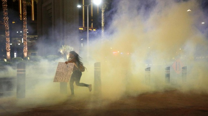 A protester runs through tear gas on the Las Vegas Strip on Sunday, May 31, 2020, in Las Vegas, during demonstrations over the death of George Floyd, who died May 25 after he was pinned at the neck by a Minneapolis police officer. (AP Photo/Steve Marcus)