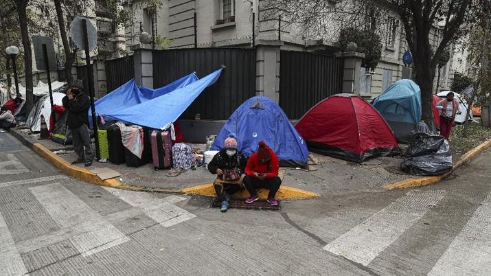 Para pekerja migran asal Peru membangun tenda di luar gedung konsulat Peru untuk menuntut repatriasi di tengah pandemi COVID-19 di Santiago, Chili. AP/Esteban Felix