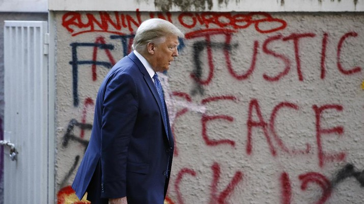 President Donald Trump walks from the White House past graffiti in Lafayette Park to visit St. John's Church in Washington on Monday, June 1, 2020. (AP Photo/Patrick Semansky)