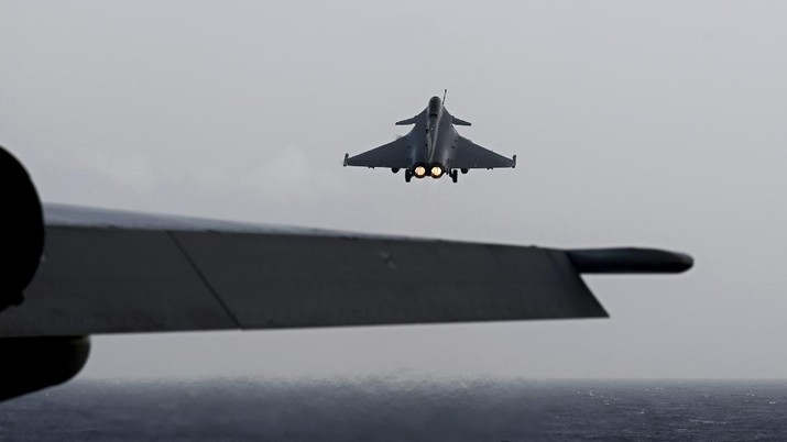 A Rafale fighter jet lands on deck of the French aircraft carrier Charles de Gaulle, off the coast of the city of Hyeyres, southern France, Thursday, Jan. 23, 2020. France deploys the Charles de Gaulle aircraft carrier for a three-month mission to support International military operations in the Middle East, French President Emmanuel Macron said. (Philippe Lopez/Pool Photo via AP)