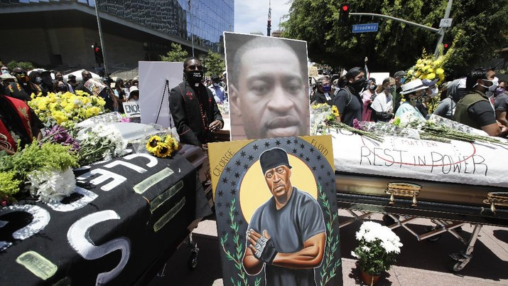 Pastor Eddie Anderson, center, of McCarty Memorial Church, stands behind caskets and and image of George Floyd, Monday, June 8, 2020, in Los Angeles during a protest over the death of Floyd on May 25 after he was restrained by Minneapolis police.. (AP Photo/Marcio Jose Sanchez)