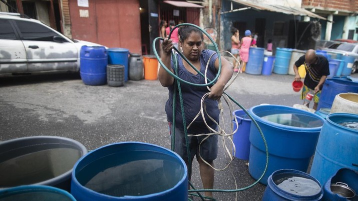 A woman untangles an electrical cord and a hose in order to pump from a large container water provided by a government water truck, in the Petare slum of Caracas, Venezuela, Wednesday, June 10, 2020. Amid water shortages during the COVID-19 pandemic, the government is providing free water to some areas. (AP Photo/Ariana Cubillos)