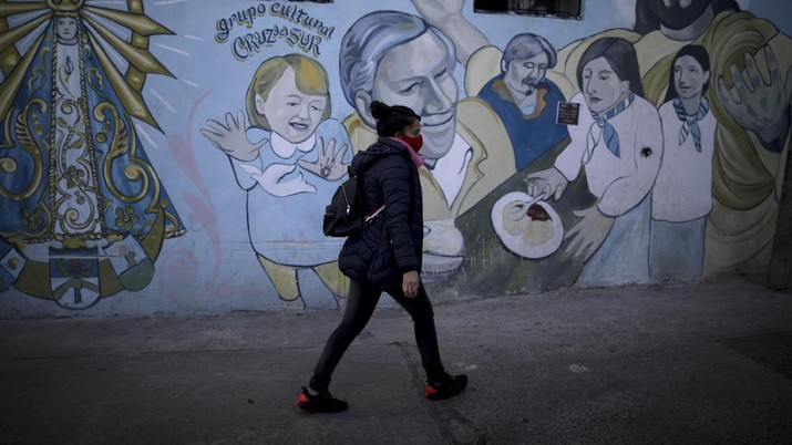 In this June 2, 2020 photo, parish assistant Natividad Benitez serves a hot drink outside a church, during a government-ordered lockdown to curb the spread of the new coronavirus, in the Villa 1-11-14 shanty town of Buenos Aires, Argentina. Since coronavirus came to Argentina, the priest who employs her has gone from serving 350 meals a day to 7000, feeding residents of the poor neighborhood where economic activity has all but stopped due to strict anti-virus measures.  (AP Photo/Natacha Pisarenko)
