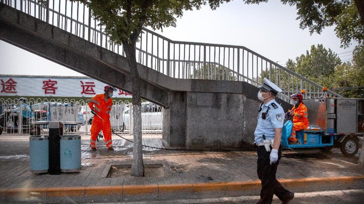 A  police officer watches as workers spray a sidewalk near the Xinfadi wholesale food market district in Beijing, Saturday, June 13, 2020. Beijing closed the city's largest wholesale food market Saturday after the discovery of seven cases of the new coronavirus in the previous two days. (AP Photo/Mark Schiefelbein)