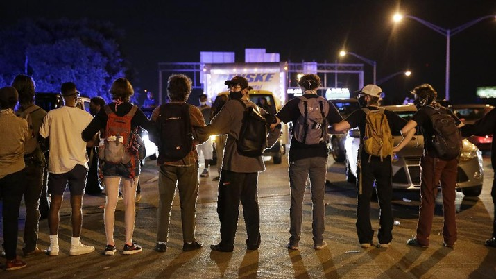 A person is covered with liquid after being officials deployed teargas at protesters Saturday, June 13, 2020, near the Atlanta Wendy's where Rayshard Brooks was shot and killed by police Friday evening following a struggle in the restaurant's drive-thru line in Atlanta. (AP Photo/Brynn Anderson)