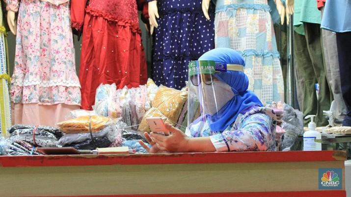 Suasana Pasar Tanah Abang resmi dibuka kembali hari ini setelah sebelumnya tutup karena pembatasan sosial berskala besar (PSBB) DKI Jakarta. 15/6/20, CNBC Indonesia/Tri Susilo Pantauan CNBC Indonesia di Ruko Blok B Pasar Tanah Abang, Jakarta Pusat, Senin (15/6/2020), kawasan ruko ini didominasi oleh pedagang baju, kain dan kerudung. Setiap pengunjung berjalan, pedagang pun menjajakan barang jualannya.    Sebelum memasuki pasar pengunjung dicek suhu oleh dinas kesehatan setempat dan pihak pengelola mal sudah menyediakan tempat cuci tangan di setiap Blok pintu masuk pasar.  Terdapat masyarakat dan pedagang yang sedang melalukan transaksi jual-beli. Mereka bertransaksi menggunakan masker. Namun, hanya sedikit pedagang yang menggunakan face shield.  Mayoritas pengunjung membeli barang dalam jumlah yang banyak. Bahkan, tak jarang pengunjung datang dengan membawa trolly lipat untuk memudahkannya membawa barang.   Seperti diketahui, Perumda Pasar Jaya menerapkan sistem ganjil-genap di pasar-pasar yang dikelolanya. Skema ganjil-genap di pasar berlaku sesuai dengan nomor kios, misalnya apabila tanggal genap, maka kios yang bukan hanya bernomor genap.  Direktur Utama Perumda (PD) Pasar Jaya Arief Nasrudin mengatakan aturan ganjil-genap di pasar di wilayah DKI Jakarta akan berlaku pada 15 Juni 2020. Aturan tersebut diberlakukan untuk mencegah semakin masifnya penularan Virus Corona (COVID-19) di pasar. (CNBC Indonesia/Tri Susilo)