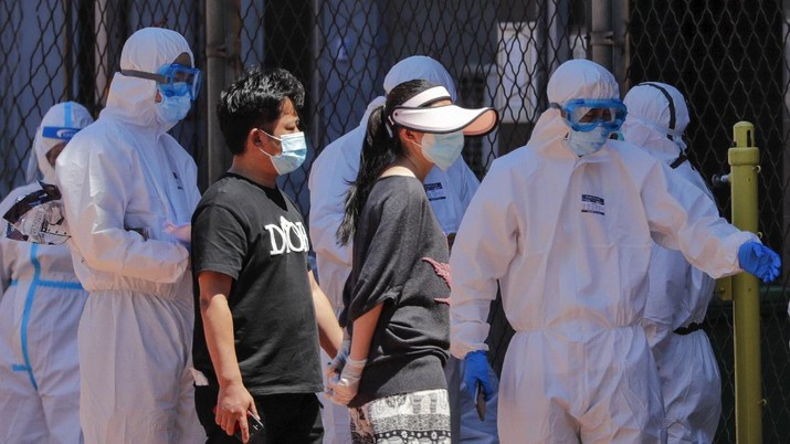 Workers in protective suits direct people who was either living surrounding the Xinfadi wholesale market or have visited to the market to get a nucleic acid test at a stadium in Beijing, Sunday, June 14, 2020. China is reporting its highest daily total of coronavirus cases in two months after the capital's biggest wholesale food market was shut down following a resurgence in local infections. (AP Photo/Andy Wong)