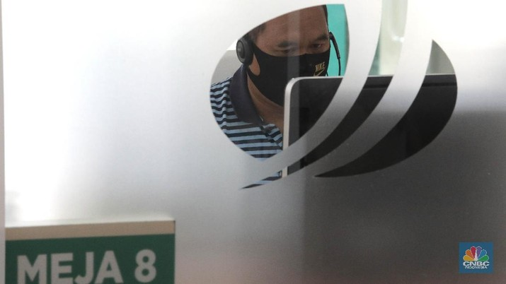 Peserta BP Jamsostek konsultasi layanan tanpa kontak fisik dengan virtual di Kantor Cabang BPJS Ketenagakerjaan Cilandak, Kamis (18/6/2020). Layanan secara virtual ini merupakan penerapan sesuai dengan protokol kesehatan tanpa harus kontak langsung antara petugas dan peserta BP Jamsostek dalam rangka mencegah penularan COVID-19. Kepala Kantor Cabang Puspitaningsih mengatakan adanya layanan konsultasi tanpa kontak fisik ini di Cabang Cilandak ini disesuaikan dengan aturan protokol kesehatan dan untuk memutus penyebaran Covid-19.  Kantor cabang ini menyediakan skat-skat yang dilengkapi layar monitor yang terhubung dengan petugas secara video conference untuk kebutuhan komunikasi dan verifikasi data.