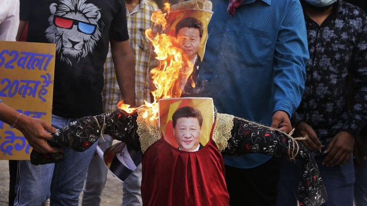 Indians burn an effigy of Chinese President Xi Jinping during a protest against China in Ahmedabad, India, Thursday, June 18, 2020. Twenty Indian troops were killed in a clash with Chinese soldiers in the Galwan Valley area Monday night that was the deadliest conflict between the sides in 45 years. (AP Photo/Ajit Solanki)