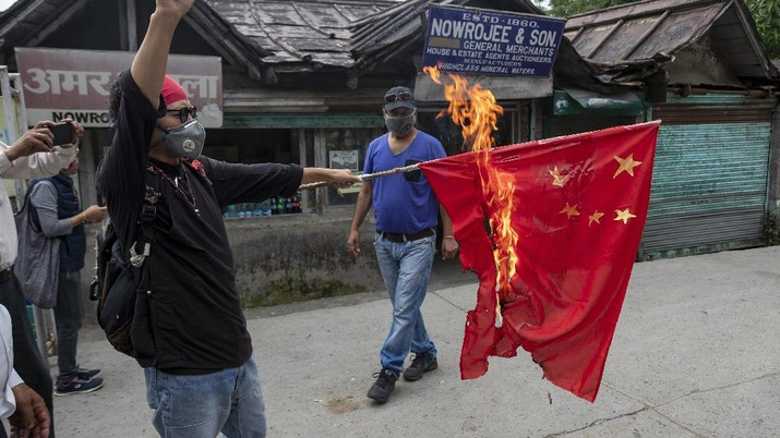 Tenzin Tsundue, an exile Tibetan activist burns a Chinese national flag during a one-man protest in Dharmsala, India, Thursday, June 18, 2020. Tsundue, said he was burning the flag as a symbolic protest against Chinese invasion of Indian territory and its continued occupation of Tibet. Twenty Indian troops were killed in a clash with Chinese soldiers in the Galwan Valley area Monday night that was the deadliest conflict between the sides in 45 years. (AP Photo/Ashwini Bhatia)