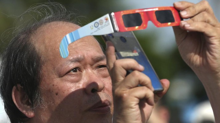 A man tries to take photos as a solar eclipse is seen over the sky in Chiayi City, southwest of Taiwan, Sunday, June 21, 2020. (AP Photo/Chiang Ying-ying)