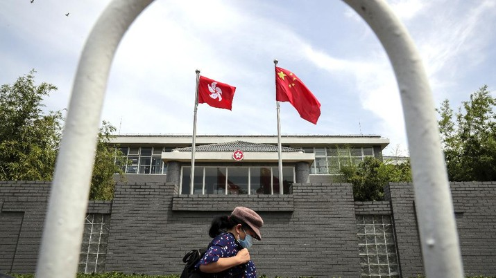 A woman wearing a protective face mask walks by the Government of Hong Kong Special Administrative Region office building in Beijing, Tuesday, June 30, 2020. Hong Kong media are reporting that China has approved a contentious law that would allow authorities to crack down on subversive and secessionist activity in Hong Kong, sparking fears that it would be used to curb opposition voices in the semi-autonomous territory. (AP Photo/Andy Wong)