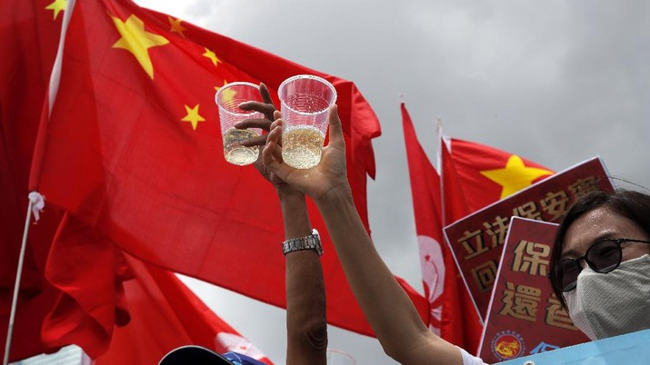 Pro-China supporters holding Chinese national flags, toast during a rally to celebrate the approval of a national security law for Hong Kong, in Hong Kong, Tuesday, June 30, 2020. Hong Kong media are reporting that China has approved a contentious law that would allow authorities to crack down on subversive and secessionist activity in Hong Kong, sparking fears that it would be used to curb opposition voices in the semi-autonomous territory. (AP Photo/Kin Cheung)