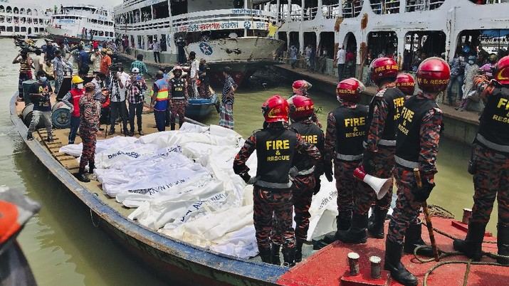 People watch as rescuers bring bodies of passengers recovered from Buriganga River in Dhaka, Bangladesh, Monday, June 29, 2020. A ferry carrying about 100 passengers capsized after being hit Monday by a larger vessel in a Bangladeshi river, killing at least 28 people, officials said. (AP Photo/Al-emrun Garjon)