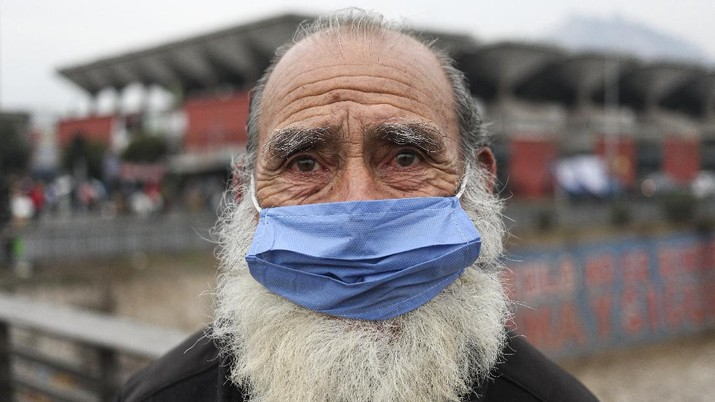 A man wearing a protective face mask as a precaution amid the new coronavirus pandemic, poses for a photo after buying groceries at a market in Santiago, Chile, Monday, June 8, 2020.  With Latin America now the epicenter of the pandemic, but with hundreds of millions relying on these markets for food and livelihoods, the debate now centers on whether and how they can operate safely. (AP Photo/Esteban Felix)