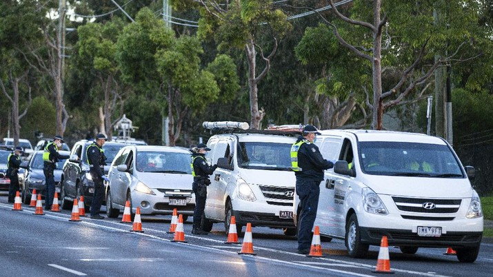 Police check drivers at a roadblock in suburban Melbourne, Australia, Thursday, July 2, 2020. Thousands of residents in dozens of suburbs of Melbourne, are preparing to lockdown for a month with the Victoria state premier warning a state-wide shutdown is possible if coronavirus cases continue to rise. (Daniel Pockett/AAP Image via AP)