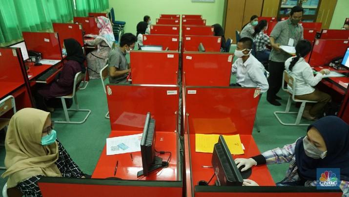 Peserta mengikuti Ujian Tulis Berbasis Komputer (UTBK) di SMKN 46 Jakarta, Senin (6/7/20). SMKN 46, Jakarta menyelenggarakan ujian dalam dua tahap yakni sesi 1 dan sesi 2, dibagi pada pukul 09.00 WIIB dan sesi 2, 14.00 WIB   Jumlah keseluruhan peserta untuk 1 sesi mencapai 90 orang.    Pelaksanaan UTBK tersebut menerapkan protokol kesehatan, termasuk memakai masker dan sarung tangan.       Di Jakarta, protokol ini diikuti oleh para peserta UTBK di SMKN 46 Jakarta sebagaimana dilaporkan CNBC Indonesia Selama beberapa jam, para peserta UTBK yang bermasker dan memakai sarung tangan tampak berkonsentrasi mengerjakan soal ujian di hadapan komputer masing-masing. Beberapa di antara mereka juga memakai face shield.  (CNBC Indonesia/ Tri Susilo)