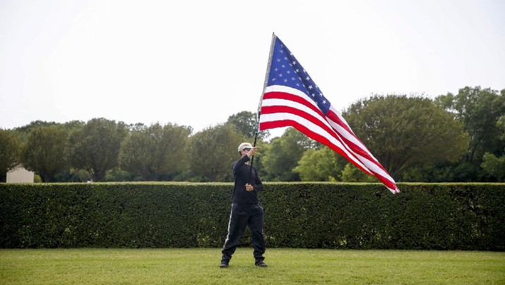 A spectator waves an American flag during the processional for Tulsa Police Sgt. Craig Johnson in front of Floral Haven Cemetery on Thursday, July 9, 2020, in Tulsa, Okla. Johnson was shot during a traffic stop on June 29. (Ian Maule/Tulsa World via AP)