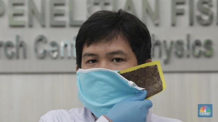 Tim Peneliti Fisika LIPI, Puspitek Tangerang Selatan berhasil mengembangkan masker kain disinfektor berlapis tembaga yang mampu membunuh virus Covid-19 dalam waktu 4 jam.  Jumat (10/7/20). CNBC Indonesia/Tri Susilo Lembaga Ilmu Pengetahuan Indonesia (LIPI) melakukan riset pada masker kain sebagai upaya penanganan Covid-19 di Indonesia. Inovasi masker ini diperuntukan bagi masyarakat umum, bukan tenaga medis. Peneliti Pusat Penelitian Fisika LIPI Deni Shidqi Khaerudini menyatakan, timnya sedang mengembangkan masker kain disinfektor berbasis lapisan tembaga yang diyakini anti Covid-19. Ini berdasarkan beberapa penelitian terkait tembaga sebagai anti-microbial agent. Penelitian tersebut di antaranya menunjukkan bahwa tembaga telah dikenal sebagai anti-microbial agent (agen anti mikroba) sejak zaman Mesir dan Yunani kuno, seperti untuk perawatan luka dan sterilisasi air. Selain itu, ditemukan terjadinya perusakan bakteri maupun virus akibat kontak dengan tembaga (contact killer), meski berbeda-beda tergantung jenis mikroorganisme. Secara umum, mekanisme perusakan terjadi dengan ion-ion tembaga yang mudah terlepas setelah bakteri atau virus menempel pada lapisan tembaga. Hal ini mengakibatkan kerusakan pada dinding sel dan degradasi DNA atau RNA, sehingga mikroba tidak mampu reproduksi yang berujung pada kematian sel tersebut. Terkait SARS-CoV-2 atau virus corona penyebab Covid-19, penelitian terbaru menunjukkan bahwa virus corona hanya mampu bertahan selama 4 jam di permukaan tembaga. Riset ini juga didasari efektivitas penyaringan (filter) mikroorganisme terhadap masker kain yang selama ini umum digunakan masyarakat untuk mencegah penularan Covid-19. Diketahui, virus corona berdiameter 0,065-0,125 mikron. Penelitian efektivitas filter masker kain didasarkan pada mikroorganisme B. Atrophaeus yang berdiameter 0,9-1,25 mikron. Hasilnya, masker kain satu lapis memiliki kemampuan filter 69,42 persen dan yang dua lapis sebesar 70,66 persen. Dengan demikian, jika dibandingkan