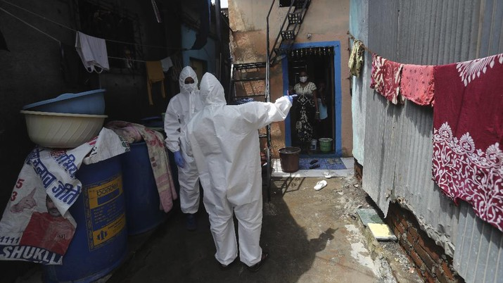 A snack vendor walks in a lane as health workers arrive to screen people for COVID-19 symptoms at a slum in Mumbai, India, Friday, July 10, 2020. India has overtaken Russia to become the third worst-affected nation by the coronavirus pandemic. (AP Photo/Rafiq Maqbool)